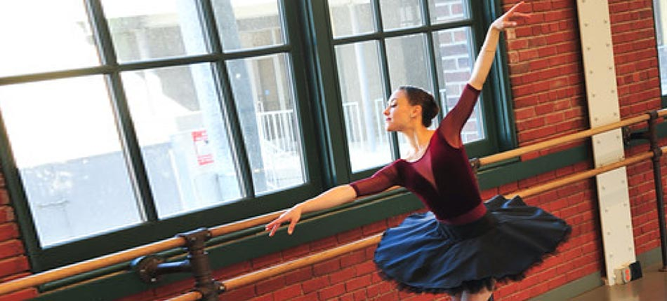 A ballerina stretching by a window